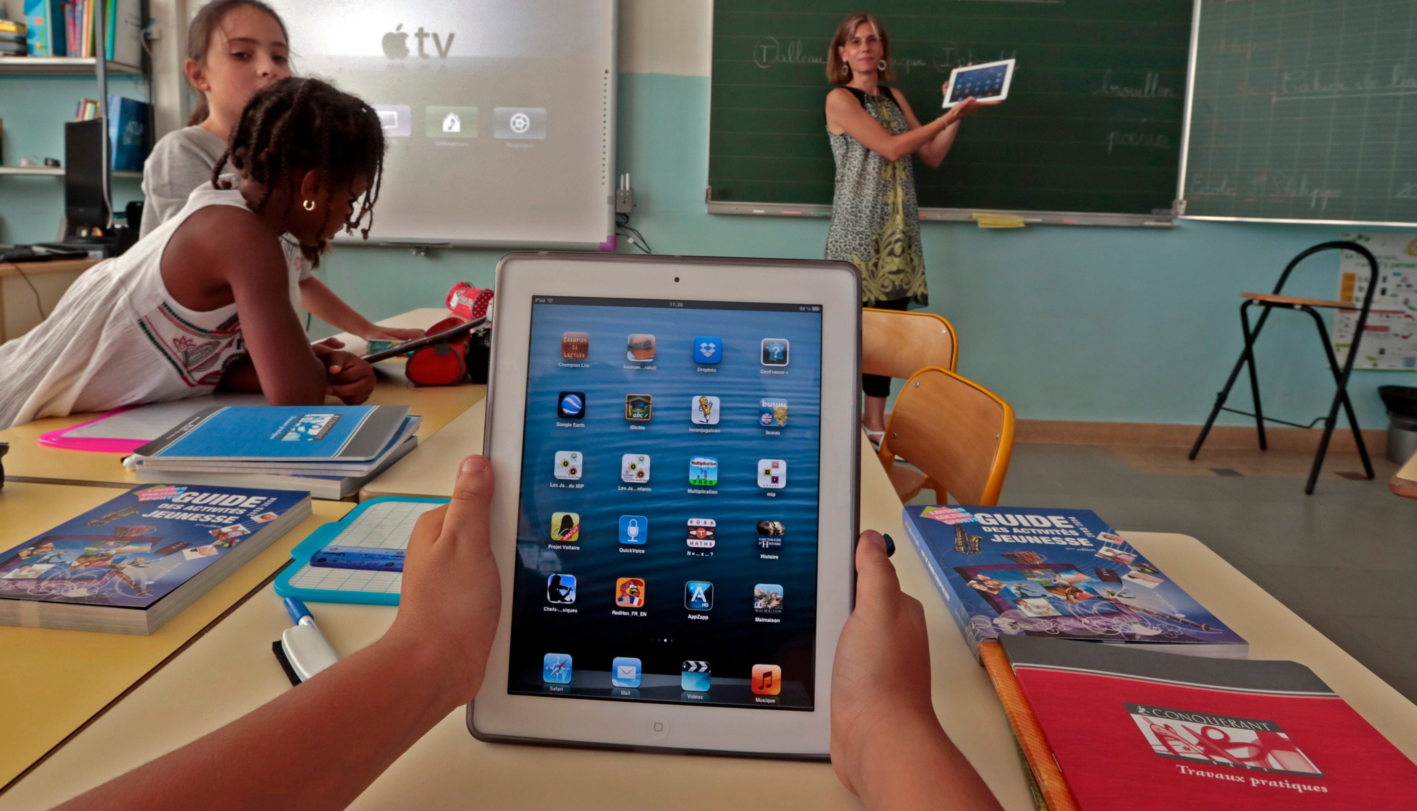 Elementary school children use electronic tablets