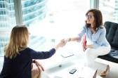 Job interview between two women shaking hands.
