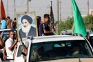 Volunteers, who have joined the Iraqi Army to fight against predominantly Sunni militants, carry weapons and a portrait of Grand Ayatollah Ali al-Sistani during a parade in the streets in Baghdad's Sadr city June 14, 2014. An offensive by insurgents that threatens to dismember Iraq seemed to slow on Saturday after days of lightning advances as government forces regained some territory in counter-attacks, easing pressure on the Shi'ite-led government in Baghdad. REUTERS/Wissm al-Okili