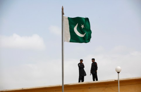 A Pakistani flag flies on a mast in front of paramilitary Frontier Corps soldiers.
