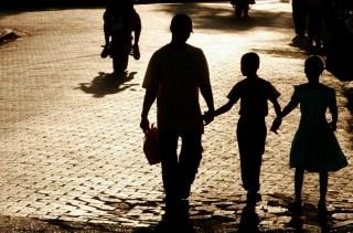 A shadowed family walks through a town.