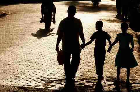 A shadowed family walks through a town.