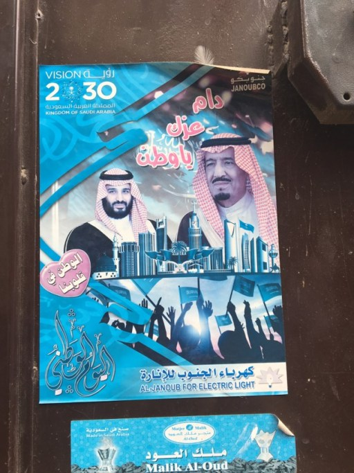 "A poster, printed by a local utility company to acclaim the king's national reform plan, called Vision 2030. Ads for Vision 2030 are omnipresent in Riyadh. We often think of the Kingdom of Saudi Arabia as a religious state, ruled by the Custodian of the Two Holy Mosques, and whose constitution is the shariah. Analysts often describe the state as a grand alliance between the ruling family and the clerical establishment, in which religious legitimacy is central. But one of the interesting features of today's Saudi Arabia is the way Saudi national identity is being pushed forward as a source of unity and legitimacy. This poster is a good example. The slogan next to King Salman says ""May your greatness be infinite, oh nation,"" and the heart next to the crown prince says ""The nation is in our hearts."""