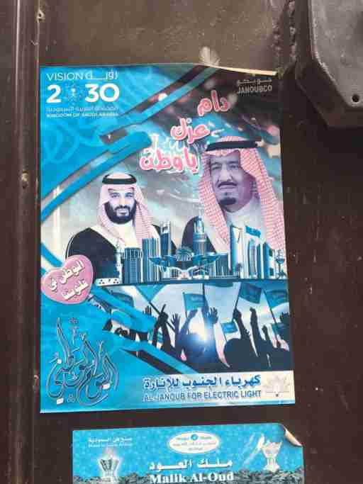 """A poster, printed by a local utility company to acclaim the king's national reform plan, called Vision 2030. Ads for Vision 2030 are omnipresent in Riyadh. We often think of the Kingdom of Saudi Arabia as a religious state, ruled by the Custodian of the Two Holy Mosques, and whose constitution is the shariah. Analysts often describe the state as a grand alliance between the ruling family and the clerical establishment, in which religious legitimacy is central. But one of the interesting features of today's Saudi Arabia is the way Saudi national identity is being pushed forward as a source of unity and legitimacy. This poster is a good example. The slogan next to King Salman says """"May your greatness be infinite, oh nation,"""" and the heart next to the crown prince says """"The nation is in our hearts."""""""