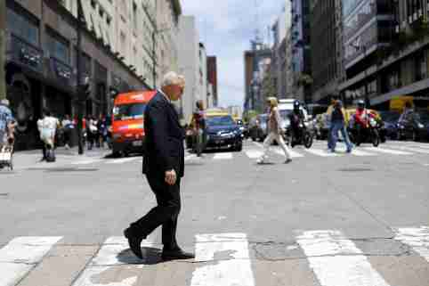 "A man crosses ""Corrientes"" avenue in a financial area in downtown Buenos Aires, Argentina, November 23, 2015. Argentine bond prices were giving back some earlier gains on Monday as investors took profits following a widely expected victory for market favorite Mauricio Macri in the presidential elections over the weekend. REUTERS/Ivan Alvarado - GF20000071141"