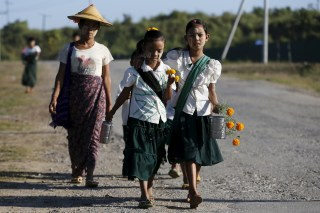 Girls walk to school at the outskirts of Yangon