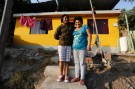 Graciela Guzman (R) and her daughter Maria pose in front of their home in Gosen City, a slum in the Villa Maria del Triunfo municipality on the outskirts of Lima April 10, 2014. Guzman was one of the founders of Gosen City more than 12 years ago, and managed to build her own home in 2009. Her daughter Maria studies graphic design in Lima. A number of residents in Gosen City, a slum that grew up near a garbage dump on the outskirts of Lima, have seen their lives improve as parts of Peru feel the effects of years of economic growth. Peru's President Ollanta Humala has pledged to cut poverty to 15 percent by the end of his term in July 2016. He is still a long way from his goal, but the poverty rate is coming down, falling just under two percentage points to 23.9 percent in 2013 from the prior year. Picture taken April 10, 2014.  REUTERS/Mariana Bazo (PERU - Tags: SOCIETY BUSINESS POLITICS POVERTY EMPLOYMENT) 
