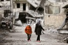 Women are seen walk near damaged buildings in Afrin, Syria March 22, 2018. REUTERS/ Khalil Ashawi - RC1ADFC75FE0