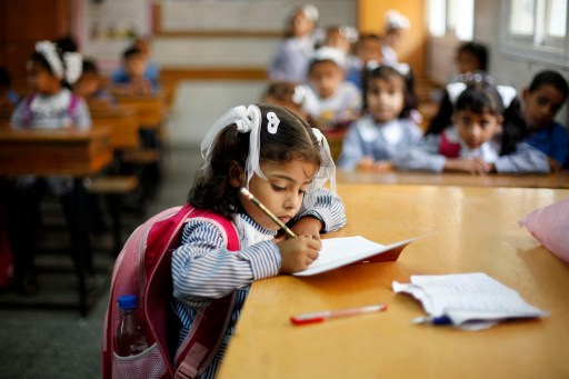 A girl writes during her class