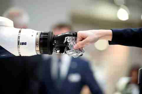 A visitor fist bumps a humanoid robot at the booth of IBG at Hannover Messe, the trade fair in Hanover