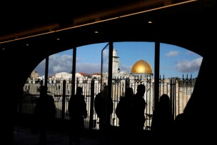 People look out from a building facing the Dome of the Rock (R), located in Jerusalem's Old City on the compound known to Muslims as Noble Sanctuary and to Jews as Temple Mount December 7, 2017. REUTERS/Ronen Zvulun - RC18733A13D0