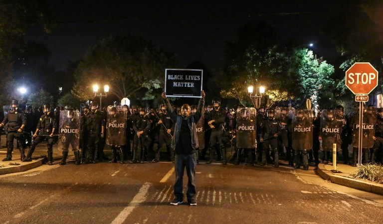 A Black Lives Matter protester stands in front of St. Louis Police Department officers equipped with riot gear after the not guilty verdict in the murder trial of Jason Stockley, a former St. Louis police officer, charged with the 2011 shooting of  Anthony Lamar Smith, who was black, in St. Louis, Missouri, U.S., September 15, 2017.  Photo taken September 15, 2017.  REUTERS/Lawrence Bryant     TPX IMAGES OF THE DAY - RC162B2292E0