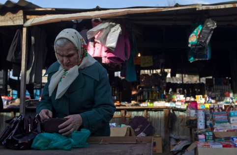 An elderly woman counts money at a market in the town of Tkvarcheli, some 50 km (31 miles) southeast of Sukhumi, the capital of Georgia's breakaway region of Abkhazia December 27, 2013. The territory of Abkhazia is located several miles southwest of the border with Russia and the Olympic Park in the Adler district of the Black Sea resort city of Sochi which will host the 2014 Winter Olympic Games in February. Abkhaz separatists fought Georgian government forces in 1992-1993, after which the breakaway region declared independence. Russia, Nicaragua, Venezuela, Nauru, Vanuatu and Tuvalu recognized Abkhazia as an independent state while all other countries regard it as a Georgian province, according to local media. Picture taken December 27, 2013. REUTERS/Maxim Shemetov (GEORGIA  - Tags: SOCIETY POLITICS OLYMPICS SPORT) - GM1EA161B4D01