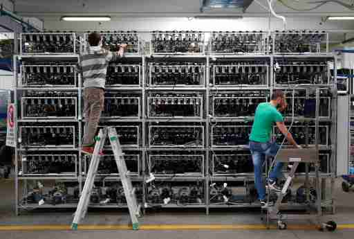 Employees work on bitcoin mining computers at Bitminer Factory in Florence, Italy, April 6, 2018. Picture taken April 6, 2018. REUTERS/Alessandro Bianchi - RC1154C44E80