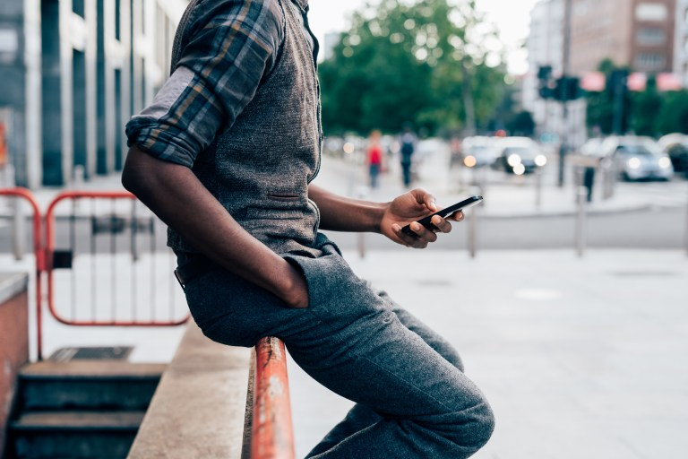 From the neck down view of young afro black man holding a smart phone, tapping the scree outdoor in the city - technology, social network, communication concept