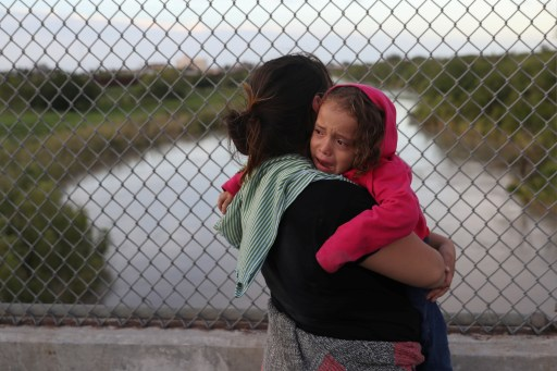 After being denied entry by U.S. Customs and Border Protection officers, an asylum seeking Honduran mother holds her crying 3-year-old daughter on the Mexican side of the Brownsville & Matamoros International Bridge near Brownsville, Texas, U.S., June 24, 2018. Picture taken June 24, 2018. REUTERS/Loren Elliott - RC1DAD0FC2D0