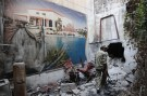 A Free Syrian Army fighter walks past a torn poster amid the rubble in the old city of Aleppo August 27, 2013. REUTERS/Muzaffar Salman (SYRIA - Tags: POLITICS CONFLICT) - GM1E98S046P01
