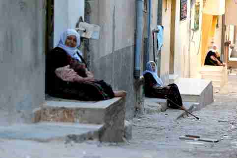Palestinian refugee women sit if front their homes during the holy month of Ramadan, in Al-Baqaa Palestinian refugee camp, near Amman, Jordan, May 29, 2018. Reuters/Muhammad Hamed - RC19116CA0A0