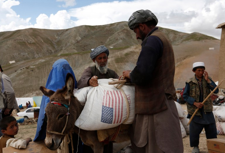 Displaced Afghans load aid near the site of a landslide at the Argo district in Badakhshan province May 5, 2014. Grief-stricken and desititute Afghan villagers vented anger with their government as they scrambled for emergency aid, three days after deadly landslides engulfed their homes. Some 300 homes in Aab Bareek, a village in the Argo district of Badakhshan, a remote and mountainous northeastern province, were buried under up to 50 metres of earth and debris. REUTERS/Mohammad Ismail (AFGHANISTAN - Tags: DISASTER) - GM1EA56055K01