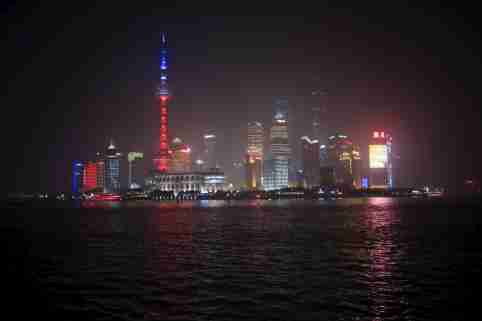 Shanghai's landmark building Oriental Pearl TV Tower is lit up in blue, white and red, the colors of the French flag, following the Paris attacks, in Shanghai, China, November 14, 2015. REUTERS/Aly Song - GF20000059181
