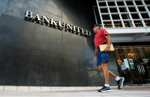 A pedestrian walks in front of the BankUnited headquarters in Coral Gables, Florida May 21, 2009. U.S. bank regulators on Thursday closed troubled lender BankUnited Financial Corp, Florida's largest bank, and sold its banking operations to a private equity consortium that includes WL Ross & Co. BankUnited, which had $12.8 billion in assets and $8.6 billion in retail deposits, is the biggest of 34 U.S. banks to fail so far this year. The Federal Deposit Insurance Corp said it estimates BankUnited's failure will cost its insurance fund $4.9 billion. REUTERS/Carlos Barria (UNITED STATES BUSINESS POLITICS) - GM1E55M0MI401