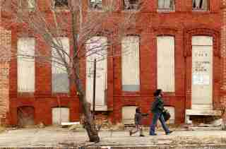 A woman and child walk past a dilapidated building in a run-down neighborhood of Baltimore, Maryland March 9, 2011. REUTERS/Kevin Lamarque (UNITED STATES - Tags: SOCIETY) - GM1E73A0I1C01