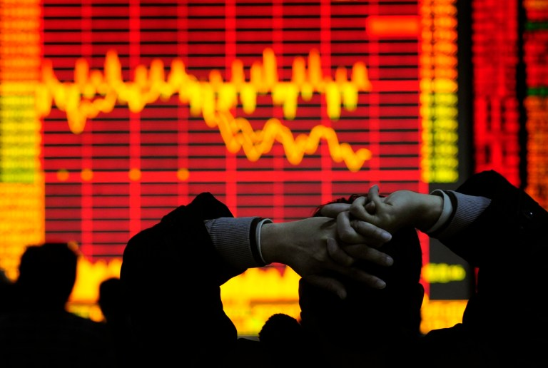An investor looks at an electronic board showing stock information at a brokerage house in Hefei, Anhui province December 9, 2008. China's stock market dropped in heavy trade on Tuesday, led by property and financial shares, on worries that November economic data, to be released in coming days, would be poor. REUTERS/Stringer (CHINA).  CHINA OUT. NO COMMERCIAL OR EDITORIAL SALES IN CHINA. - GF2E4C90PRF01