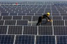 A man works on solar panels at a solar power plant of China Huaneng Group in Huaiyin, Jiangsu province, China June 13, 2018.  REUTERS/Stringer ATTENTION EDITORS - THIS IMAGE WAS PROVIDED BY A THIRD PARTY. CHINA OUT. - RC135BDD6120