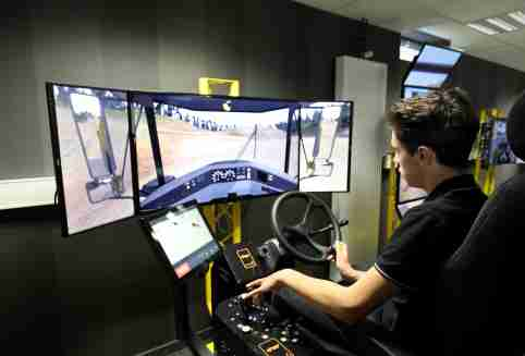 A student uses a driving simulator for civil engineering machines during a visit of the French President to The School of Application to the Trades of Public Works (EATP), which is devoted to apprenticeship and vocational training in Egletons, France, October 4, 2017.  REUTERS/Ludovic Marin/Pool - RC1A228984D0