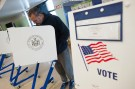 A voter casts his ballot behind a ballot booth during the U.S. presidential election at a polling station in the Staten Island Borough of New York, U.S. on November 6, 2012. REUTERS/Keith Bedford/File Photo - TM3EC7H11OV01