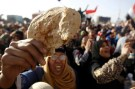 An Egyptian holds a piece of bread to protest against the high prices of goods in Tahrir square in Cairo February 8, 2013. REUTERS/Mohamed Abd El Ghany (EGYPT - Tags: POLITICS CIVIL UNREST BUSINESS) - GM1E92900KZ01