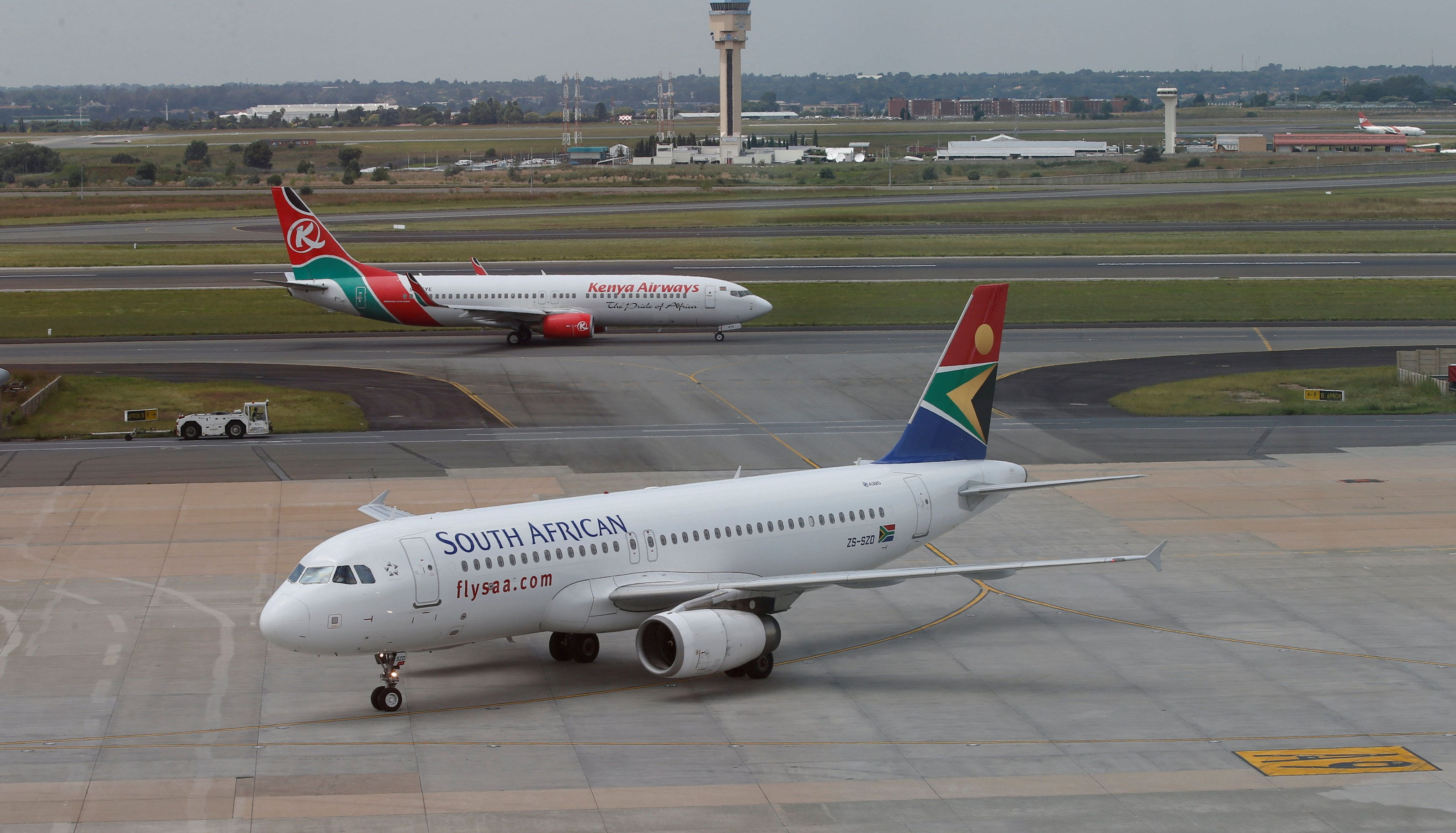 FILE PHOTO: A South African Airways Airbus A320-200 aircraft (bottom) arrives as a Kenya Airways Boeing 737-800 aircraft prepares to take off at the OR Tambo International Airport in Johannesburg, South Africa, March 8, 2017. REUTERS/Siphiwe Sibeko/File Photo - RC1E35E6C420