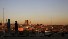 Unused cooling towers are seen overlooking an informal settlement as locals walk before sunset in Soweto, South Africa August 5, 2015. REUTERS/Siphiwe Sibeko - GF20000014477