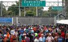 Central Americans, part of a caravan trying to reach the U.S., stand near the Mexican border gate on the bridge between Guatemala and Mexico.