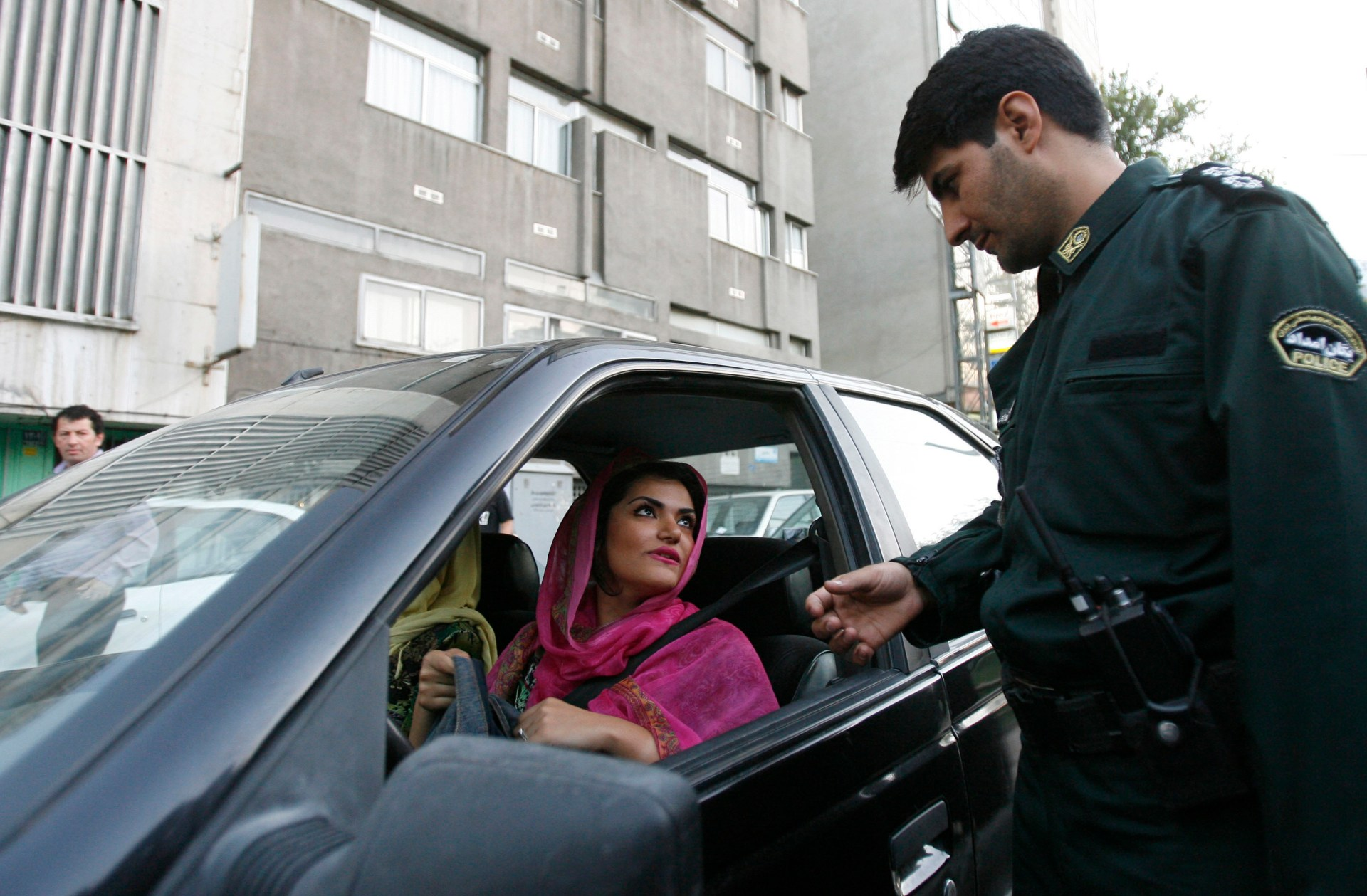 "A policeman asks a woman wearing bright coloured clothes for her identification papers at a morals police checkpoint in Tehran June 16, 2008. Iranian police have launched a more extensive crackdown on ""social corruption"" such as women flouting Islamic dress codes, the Farhang-e Ashti newspaper reported on Monday. The authorities usually launch crackdowns before the hot summer months when women like to wear lighter clothing such as calf-length pants and brightly coloured scarves pushed back to expose plenty of hair. Picture taken June 16, 2008. REUTERS/Stringer (IRAN) - GM1E46H16MY01"