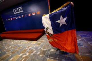 A man arranges a Chilean flag during the signing agreement ceremony for the Trans-Pacific Partnership (TPP) trade deal, in Santiago, Chile March 8, 2018. REUTERS/Ivan Alvarado - RC191708E900