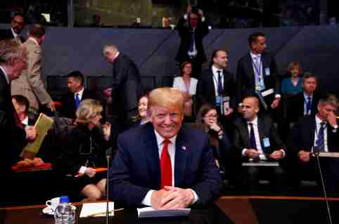"U.S. President Donald Trump attends a meeting of the North Atlantic Council during a NATO summit in Brussels, Belgium, July 11, 2018. Reuters photographer Francois Lenoir: ""I like the contrast in the photograph. The presence of U.S. President Trump posing smiling and the lack of interest of the officials in the background."" REUTERS/Francois Lenoir   SEARCH ""TRUMP POY"" FOR FOR THIS STORY. SEARCH ""REUTERS POY"" FOR ALL BEST OF 2018 PACKAGES. TPX IMAGES OF THE DAY. - RC1B4F951220"