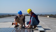 Two clean economy workers installing solar panels