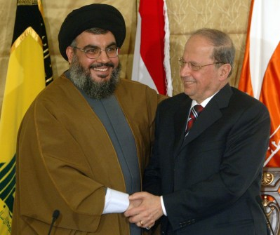 Lebanon's Hizbollah leader Sheikh Hassan Nasrallah (L) shakes hands with compatriot Christian leader Michel Aoun during a news conference in a church in Beirut, Lebanon February 6, 2006. The Chief of Lebanon's Hizbollah joined forces on Monday with Maronite Christian leader Michel Aoun to call for normal diplomatic ties with Syria. REUTERS/Mohamed Azakir - RP3DSFCZIEAB