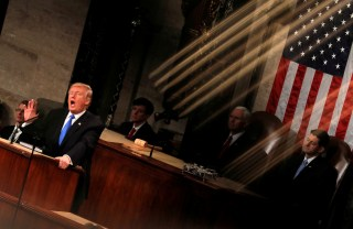 """U.S. President Donald Trump and Vice President Mike Pence are seen behind the reflection of a House chamber railing as Trump delivers his State of the Union address to a joint session of the U.S. Congress on Capitol Hill in Washington, U.S., January 30, 2018. Reuters photographer Carlos Barria: """"The State of the Union speech is one of the most important political events at the beginning of the year. We usually photograph it from several fixed positions, but this year I was assigned to be the 'rotating' photographer, meaning I could move around on the balcony and shoot from different angles, but only during short windows of time. During one of those windows, I found an interesting play of light reflected off a gold-colored railing, which, at a certain angle, could be seen to fall over the president."""" REUTERS/Carlos Barria    SEARCH """"TRUMP POY"""" FOR FOR THIS STORY. SEARCH """"REUTERS POY"""" FOR ALL BEST OF 2018 PACKAGES. TPX IMAGES OF THE DAY. - RC19E32723F0"""