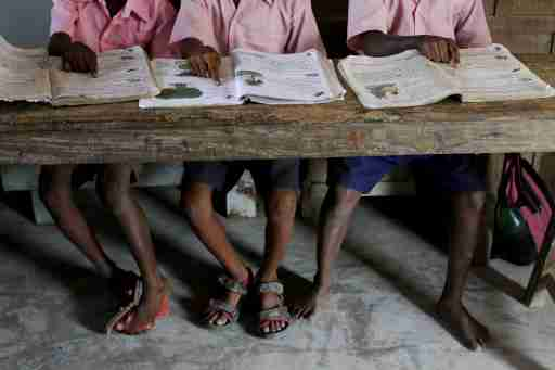 "Students from a primary school read books inside a classroom on Ghoramara Island, India, November 16, 2018. Ghoramara Island, part of the Sundarbans delta on the Bay of Bengal, has nearly halved in size over the past two decades, according to village elders. REUTERS/Rupak De Chowdhuri  SEARCH ""CHOWDHURI COASTLINE"" FOR THIS STORY. SEARCH ""WIDER IMAGE"" FOR ALL STORIES. - RC16F935BB30"