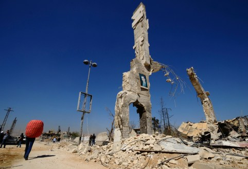 A picture of Syria's President Bashar al-Assad is displayed on a damaged structure at the entrance of al-Dukhaneya neighbourhood near Damascus, as civilians carry their belongings recovered from their homes after soldiers loyal to Syria's President Bashar al-Assad regained control of the area from rebel fighters October 7, 2014. REUTERS/Omar Sanadiki   (SYRIA - Tags: POLITICS CIVIL UNREST CONFLICT TPX IMAGES OF THE DAY) - GM1EAA71PL001