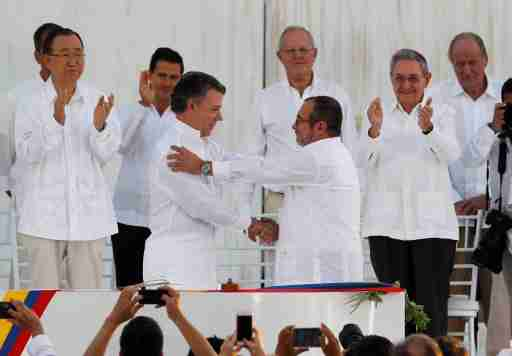 Colombian President Juan Manuel Santos (L) and Marxist rebel leader Timochenko shake hands after signing an accord ending a half-century war that killed a quarter of a million people, in Cartagena, Colombia September 26, 2016. REUTERS/John Vizcaino     TPX IMAGES OF THE DAY      - S1BEUDPIFPAA
