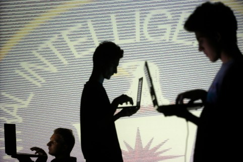 People are silhouetted as they pose with laptops in front of a screen projected with binary code and a Central Inteligence Agency (CIA) emblem, in this picture illustration taken in Zenica October 29, 2014.     REUTERS/Dado Ruvic (BOSNIA AND HERZEGOVINA  - Tags: BUSINESS SCIENCE TECHNOLOGY BUSINESS LOGO)   - LR1EAAT10ZU9I