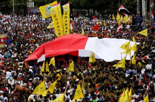 A large Indonesian flag is carried over the crowd at a rally calling for national unity and tolerance in central Jakarta, Indonesia December 4, 2016. REUTERS/Darren Whiteside - RC127395AEE0