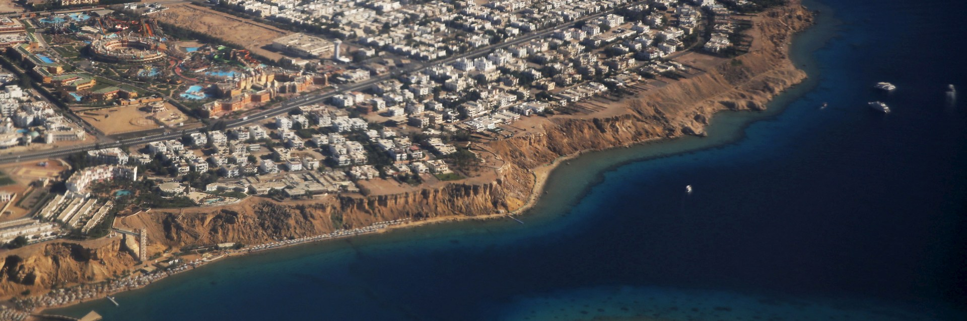 An aerial view of part of the Red Sea coast, with hotels and resorts in Sharm el-Sheikh, is seen through the window of an airplane, Egypt, December 7, 2015. REUTERS/Amr Abdallah Dalsh - GF10000257526