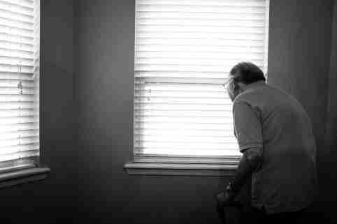 elderly man looks out the window