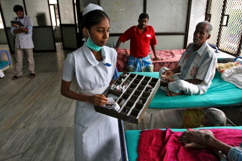 A paramedic distributes free medicine provided by the government to patients inside a ward at Rajiv Gandhi Government General Hospital (RGGGH) in Chennai July 12, 2012. Chennai is the capital of Tamil Nadu, one of two Indian states offering free medicine for all. The state provides a glimpse of the hurdles India faces as it embarks on a programme to extend free drug coverage nationwide. Picture taken July 12, 2012. To match Analysis INDIA-DRUGS/             REUTERS/Babu (INDIA - Tags: HEALTH SOCIETY DRUGS) - GM1E87N0HMY01