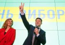 Ukrainian comic actor and presidential candidate Volodymyr Zelenskiy flashes a victory sign as his wife Olena reacts following the announcement of the first exit poll in a presidential election at his campaign headquarters in Kiev, Ukraine March 31, 2019. REUTERS/Valentyn Ogirenko - RC1FE0F095A0