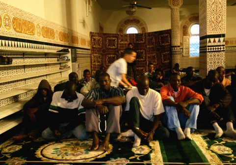 African would-be immigrants (front) pray inside a mosque near the CETI (Short-stay Immigrant Centre) during the fasting month of Ramadan in Spain's North African enclave of Melilla October 10, 2005. Morocco, under pressure to stem illegal immigration to Spain and accused by rights groups of mistreating migrants, began flying detained Africans to Senegal and Mali on Monday, government officials said. 'We have already flown 140 illegal migrants back home in Senegal this morning and we are preparing a flight of 140 others also to Senegal soon from Oujda,' a senior official told Reuters. REUTERS/Andrea Comas - RP2DSFIXLEAB